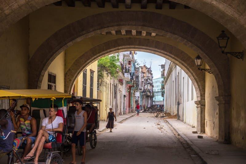 Streetscene van Cubaanse mensen in fietstaxi in oud Havana stock foto's