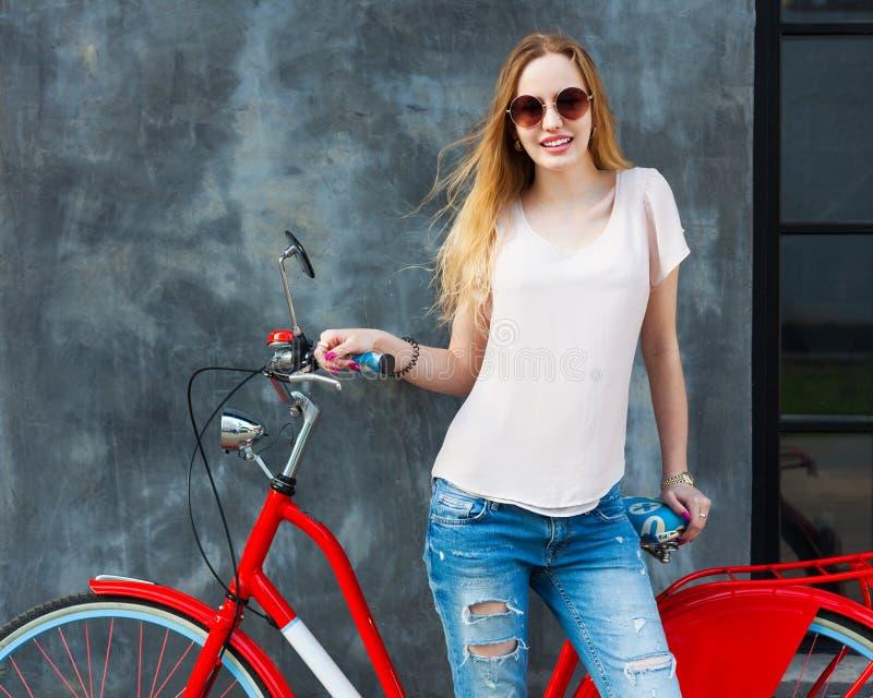 Streetstyle 摆在与一辆时髦葡萄酒红色自行车的时髦,白色成套装备的美丽的白肤金发的女孩户外 库存照片