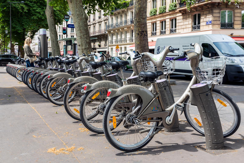 Streetview with woman paying for renting a bycicle in Paris stock photo