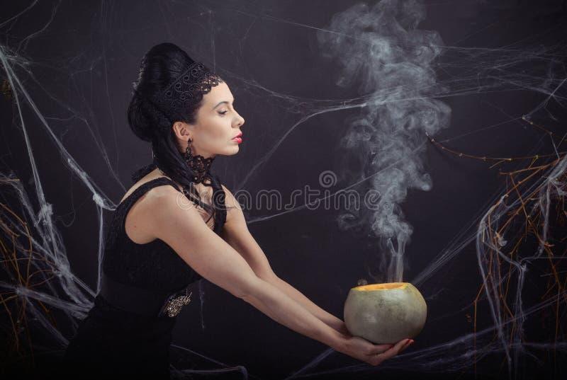 Strega cattiva del costume di Halloween e la sua pozione magica immagini stock libere da diritti