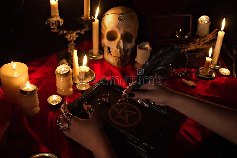 Strega che tiene un libro con il pentagramma, il cranio e le candele immagine stock