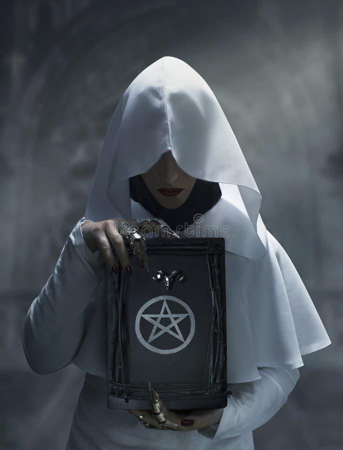 Strega che tiene un libro magico di periodo con il simbolo del pentagramma fotografie stock libere da diritti