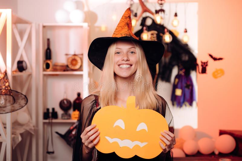 Strega di Halloween in cappello nero sulla scopa Donna che posa con la zucca Ritratto dell'interno di giovane strega sveglia al p immagini stock