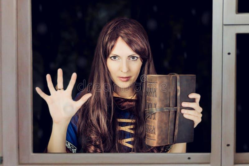 Strega di Halloween che tiene libro magico dei periodi immagine stock libera da diritti