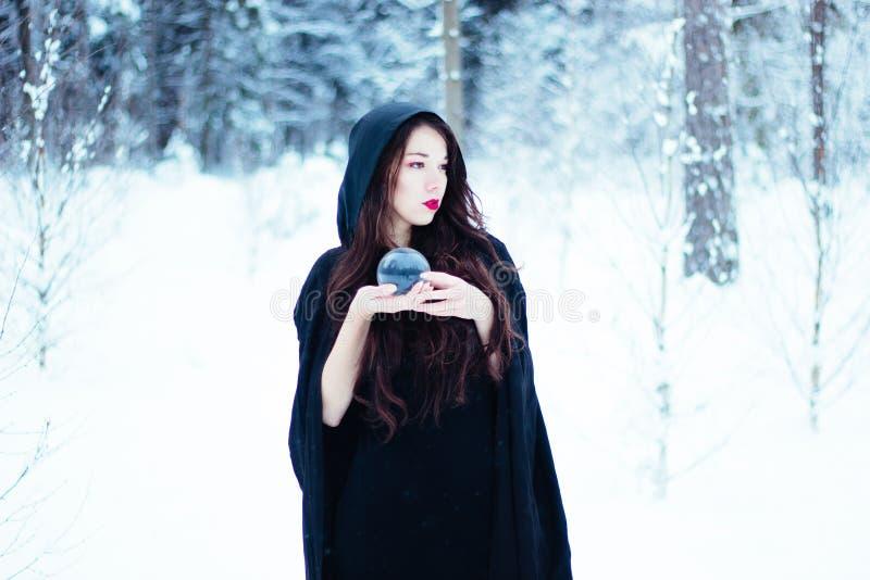 Strega in mantello nero con la palla del  del magiÑ immagini stock libere da diritti