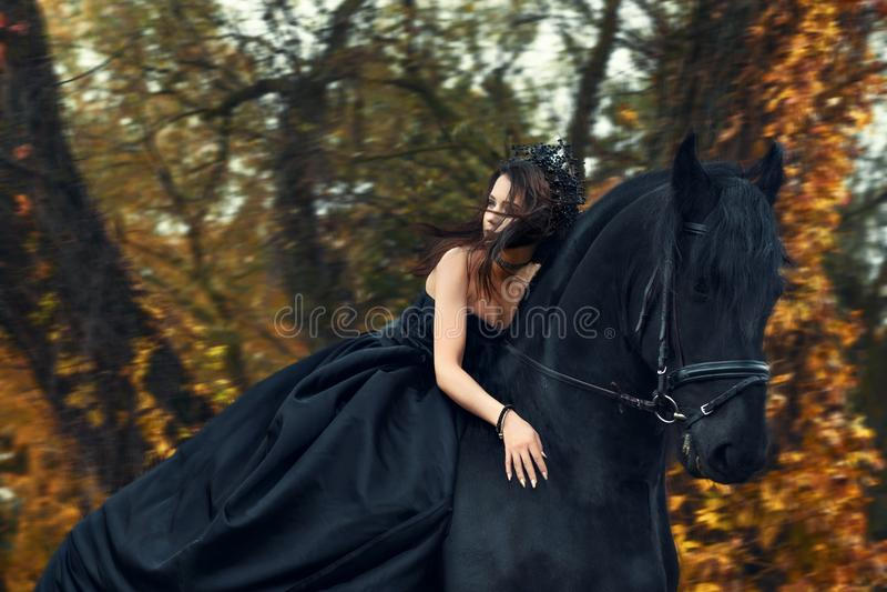 Strega nera della regina della ragazza in vestito nero e diadema che guida a cavallo su un cavallo frisone immagini stock