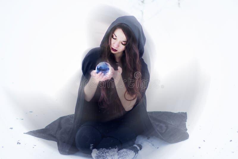 Strega o donna che fa magia in mantello nero con la palla di vetro nella foresta bianca della neve fotografia stock