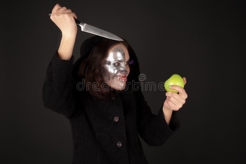 Strega Two-faced con la lama verde di cucina e della mela immagini stock libere da diritti