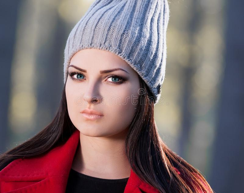 Strelnikova_Svetlana 妇女面孔红色外套和灰色帽子,蓝色骗局 库存照片