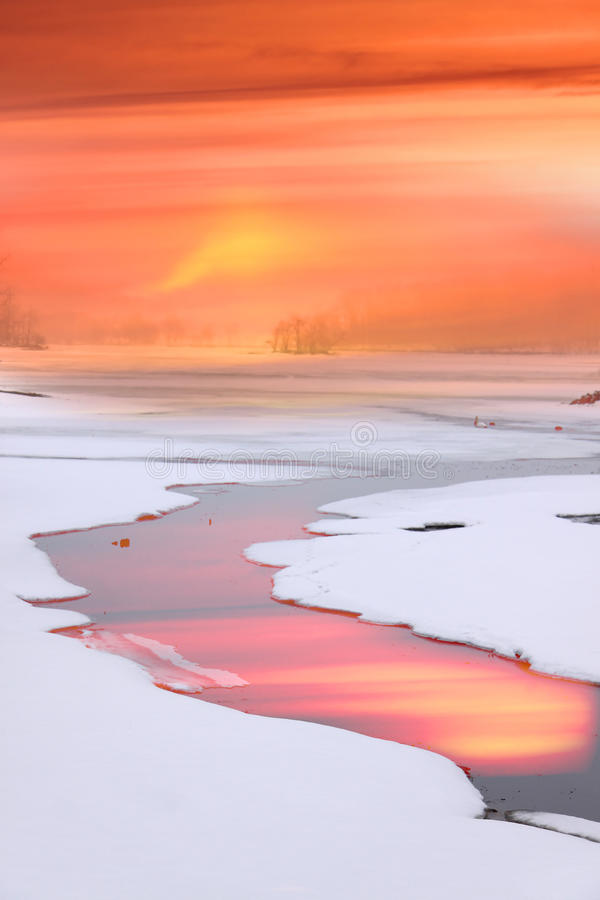 Strem flowing through frozen lake stock photography