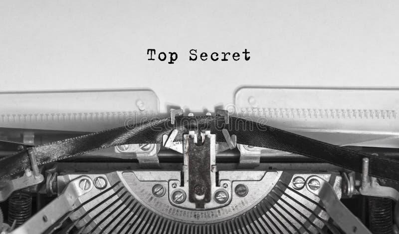 Streng geheim geschriebene Wörter auf einer Weinlese-Schreibmaschine stockfotografie