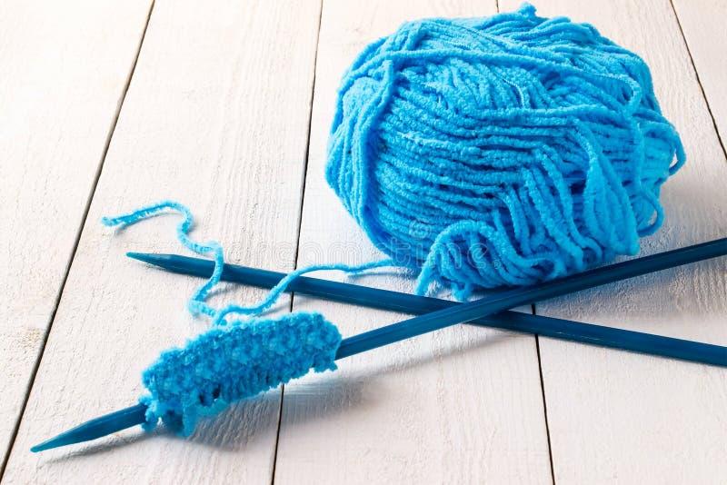 Streng van blauwe garen en naalden voor het breien stock fotografie