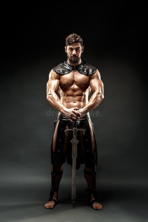 Strenge Barbaar in leerkostuum met zwaard stock afbeeldingen