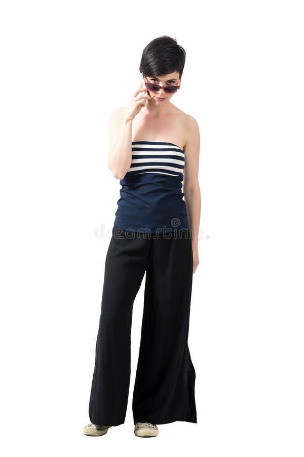 Strenge bazige jonge vrouw op de mobiele telefoon die camera over zonnebril bekijken stock afbeeldingen