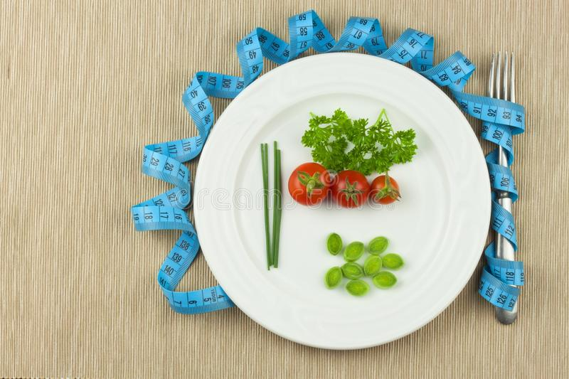 Strenge Diät gegen Korpulenz Diätetische Gemüsediät Tomaten auf einer Platte Rohes Gemüse auf einer weißen Platte und einem messe stockfoto
