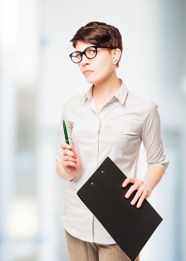 strenge ernste Geschäftsfrau mit einem Ordner in seiner Hand, die i aufwirft stockfoto