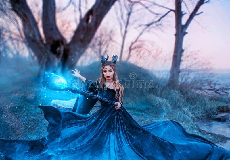 Strenge Hexe mit magischem magischem Gl?hen und Funkelnpersonal in ihren H?nden, Dame mit H?rnern auf Kopf ?u?ert Bann lizenzfreies stockbild