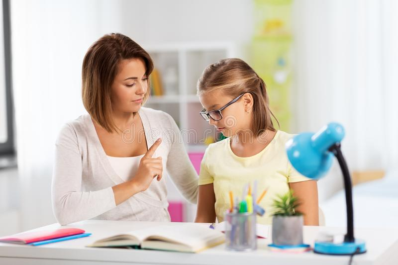 Strenge Mutter, die mit der Tochter tut Hausarbeit spricht lizenzfreie stockbilder