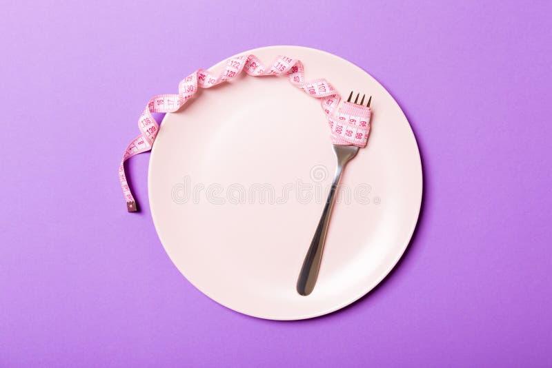 Strenges Diätkonzept mit leerem Raum für Ihren Entwurf Draufsicht der Platte mit Gabel in messendem Band auf purpurrotem Hintergr lizenzfreies stockfoto