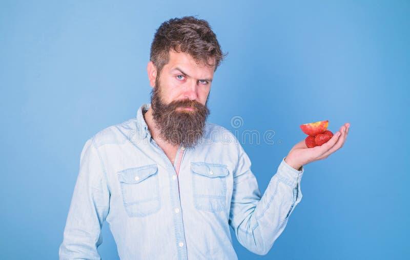 Strenges Gesicht des Mannes mit Bart bietet organische Festlichkeiten an Bärtige Grifferdbeeren und -apfel des Hippies auf Palme  stockbilder