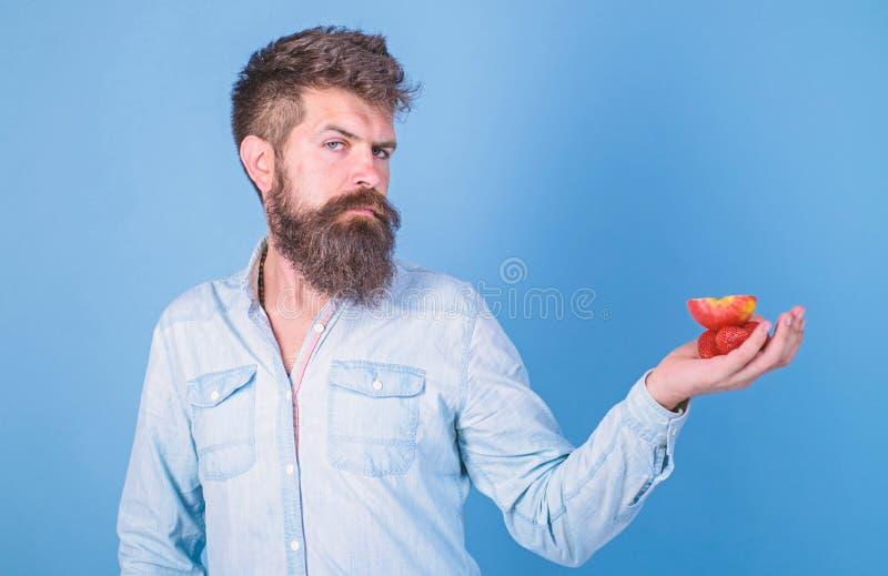 Strenges Gesicht des Mannes mit Bart bietet organische Festlichkeiten an B?rtige Grifferdbeeren und -apfel des Hippies auf Palme  lizenzfreies stockbild