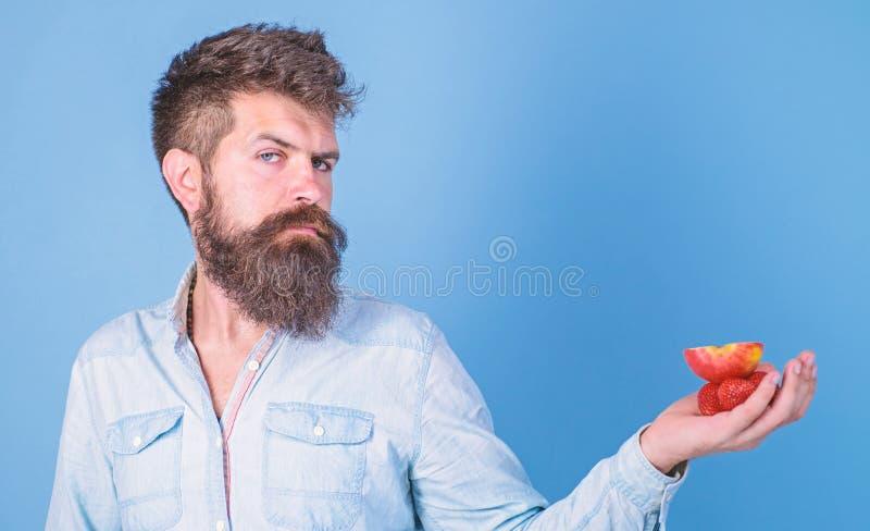 Strenges Gesicht des Mannes mit Bart bietet organische Festlichkeiten an Ich habe Festlichkeiten f?r Sie B?rtige Grifferdbeeren u lizenzfreie stockfotos