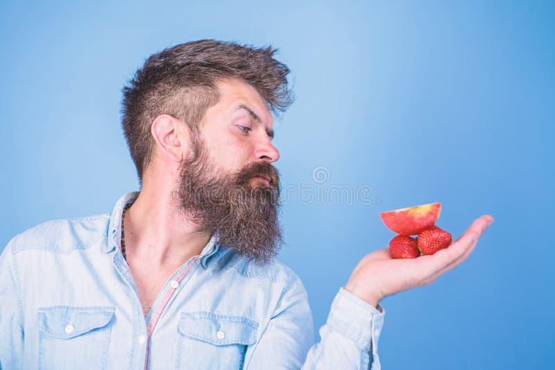 Strenges Gesicht des Mannes mit Bart bietet organische Festlichkeiten an Ich habe Festlichkeiten f?r Sie Mann bietet an, Erdbeere stockbild