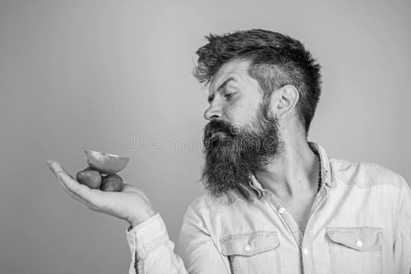 Strenges Gesicht des Mannes mit Bart bietet organische Festlichkeiten an Ich habe Festlichkeiten f?r Sie Mann bietet an, Erdbeere lizenzfreies stockfoto