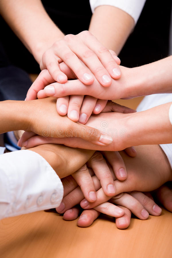 Strength. Image of business partners hands on top of each other symbolizing companionship and unity stock photo