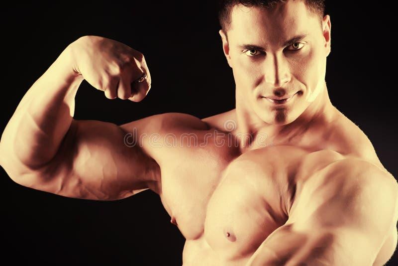 Strength concept. Handsome muscular bodybuilder posing over black background stock image