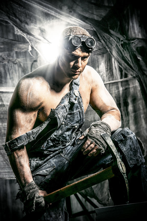 Strength. Masculine dirty coal miner with a pickaxe over dark grunge background. Mining industry. Strength. Bodybuilding royalty free stock images