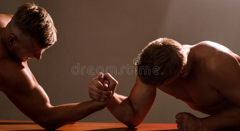 Strength and stability. Men competitors try to win victory or revenge. Twins men competing till victory. Twins. Competitors arm wrestling. Strength skills royalty free stock images