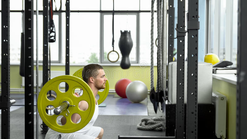 Strength training in the gym. guy doing squats with a barbell. bodybuilder doing exercise with barbell. side view royalty free stock photography