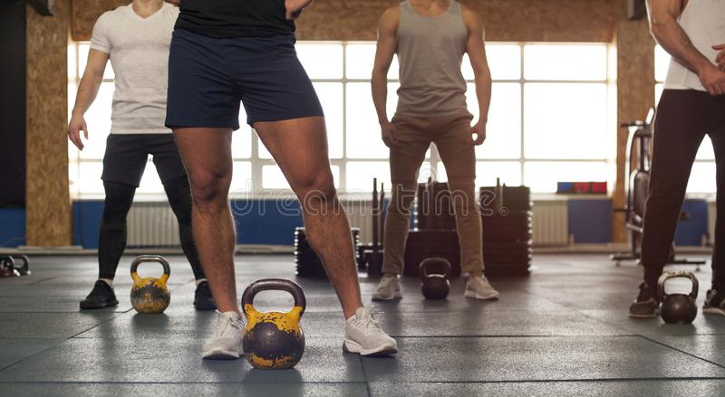 Small Group of Muscular Male Adults Lifting Kettlebells. stock photography