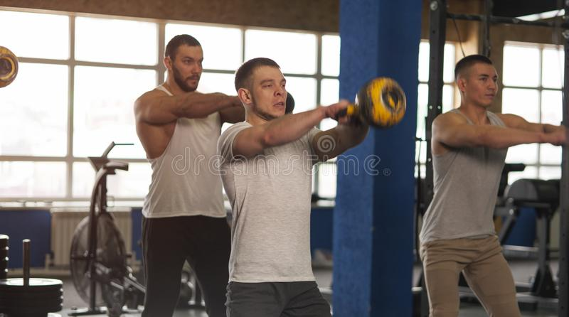 Small Group of Muscular Male Adults Working Out With Kettlebells stock images