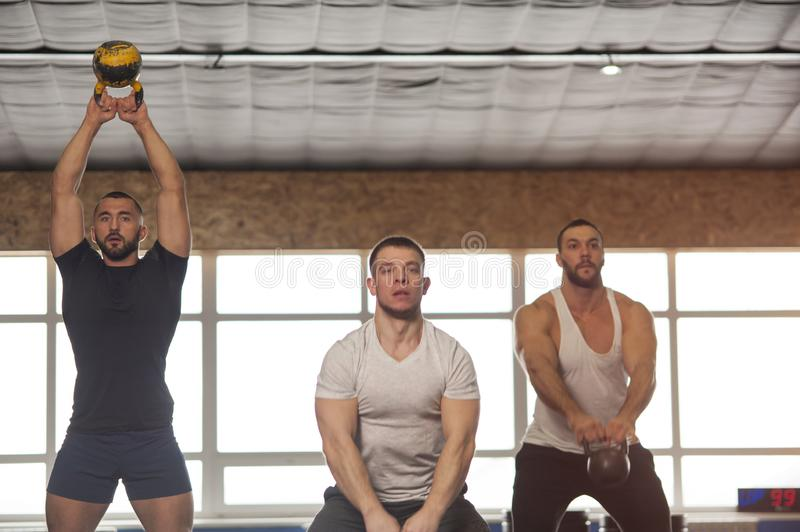 Small Group of Muscular Male Adults Working Out With Kettlebells royalty free stock photo