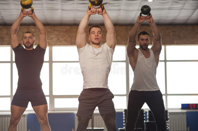 Small Group of Muscular Male Adults Working Out With Kettlebells stock image