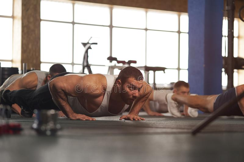 Small Group of Muscular Male Adults Warming Up Training Push Ups. stock image