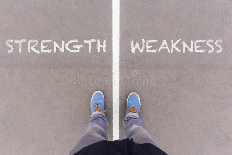 Strength and weakness text on asphalt ground, feet and shoes on. Srength and weakness text on asphalt ground, feet and shoes on floor, personal perspective royalty free stock photography