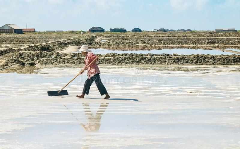 Strenuous manual labor to farm sea salt, in Cambodia. royalty free stock photography