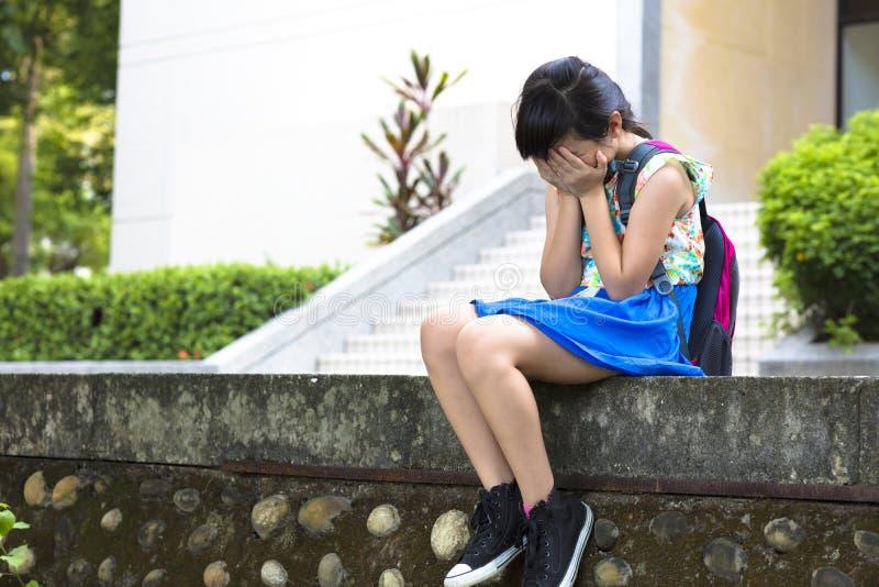 Stres dziewczyny obsiadanie w szkole zdjęcie stock