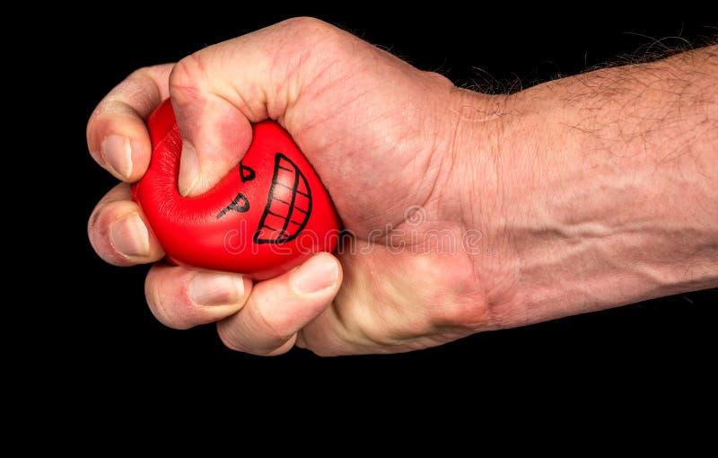 Stres piłka gniesie z śmieszną twarzą obraz stock