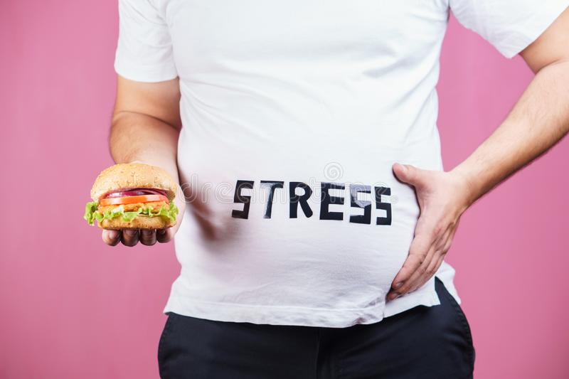 Stress, bulimia, compulsive overeating,weight gain. Stress, eating problems, bulimia, compulsive overeating, weight gain. overweight man with fresh appetizing royalty free stock image