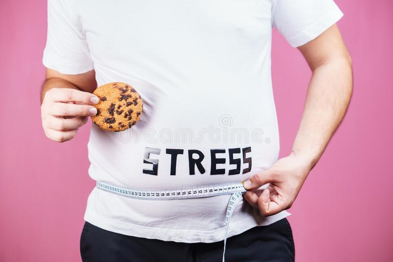 Stress, bulimia, sugar addiction, weight gain. Stress, eating problems, bulimia, compulsive overeating, sugar addiction, weight gain. overweight man with royalty free stock photography