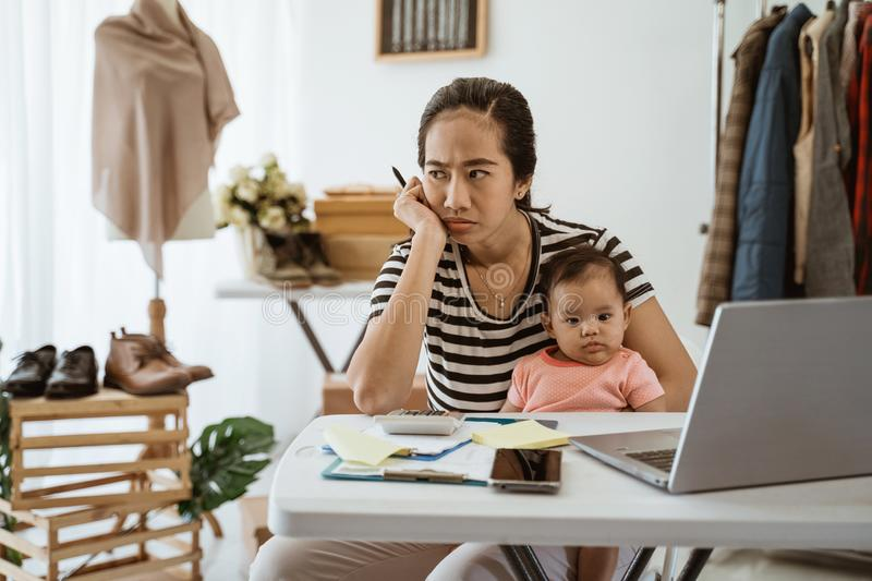 Stress business owner carrying her baby while working stock photography