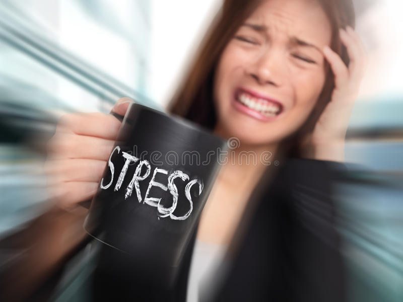 Stress - business person stressed at office. Business woman holding coffee cup with STRESS written. Overworked and over caffeinated female businesswoman royalty free stock photos