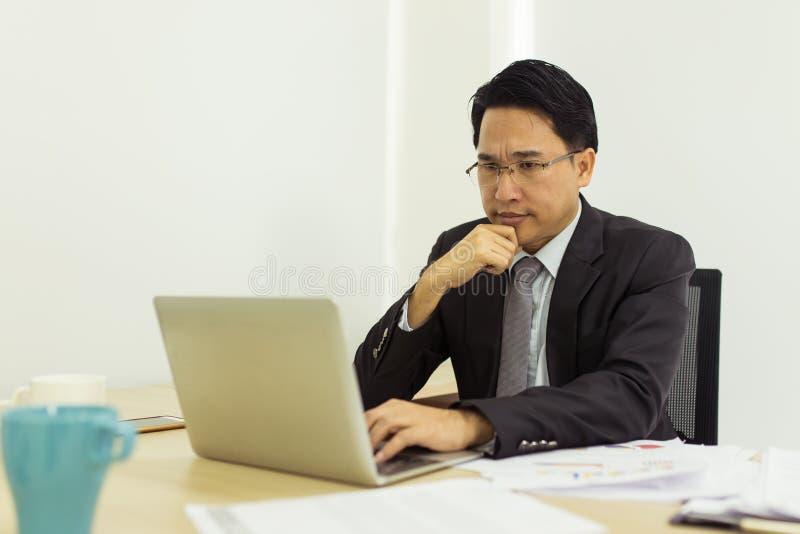 Stress businessman using laptop at his office desk stock photos