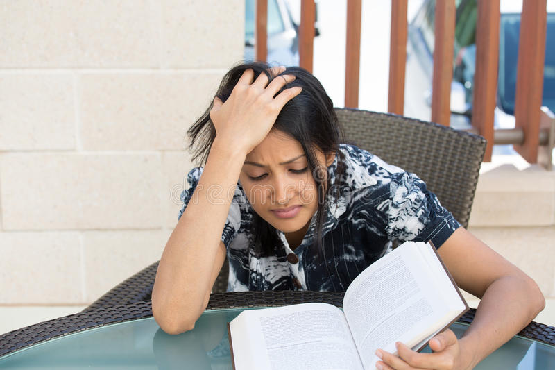 Stress. Closeup portrait, woman frustrated by what she has to read for school, hand on head, tight deadline for studying, outdoors outside background. Negative royalty free stock images