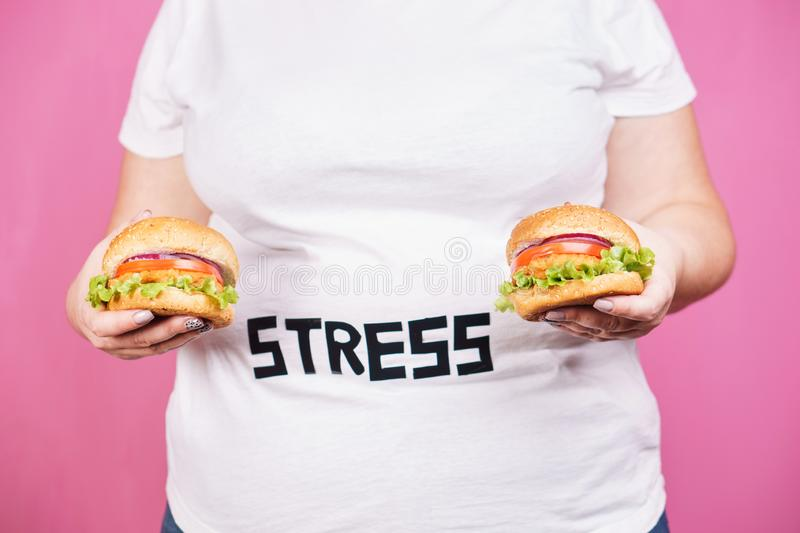 Stress, fast food, bulimia, compulsive overeating. Stress, eating problems, bulimia, compulsive overeating, weight gain. overweight woman with two burgers stock images