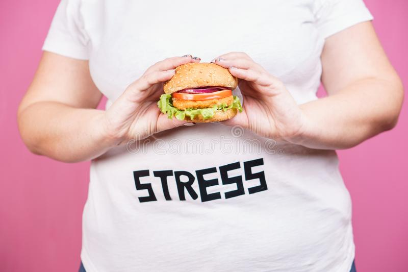 Stress, fast food, bulimia, compulsive overeating. Stress, eating problems, bulimia, compulsive overeating, weight gain. overweight woman with fresh appetizing royalty free stock images